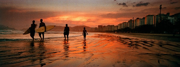 Santos Beach in Sao Paulo at sunset as two surfers head back along the shore